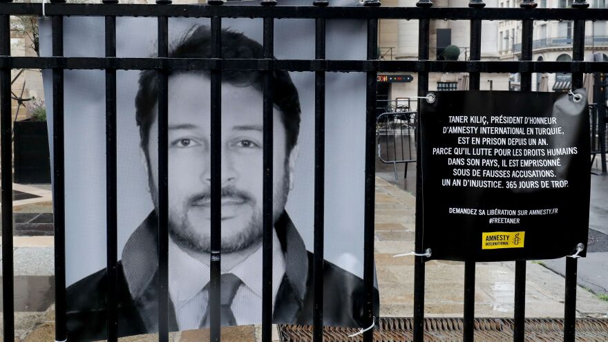 """A poster of Taner Kiliç hangs on the fence of the historic French stock market building """"Palais Brongniart"""" in Paris in June. On Wednesday, the honorary chair of Amnesty International Turkey was freed after more than a year in prison."""