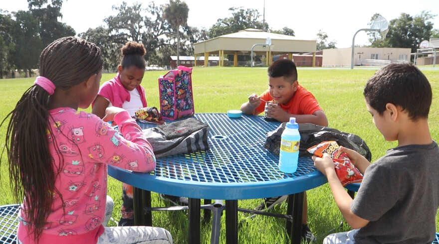 Pasco County Schools photo of four children sitting outside a school building