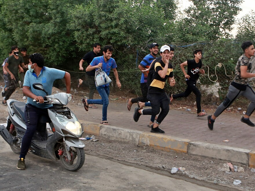 Anti-government protesters run for cover while Iraqi security forces fire live ammunition in the air during a demonstration in Baghdad on Sunday.