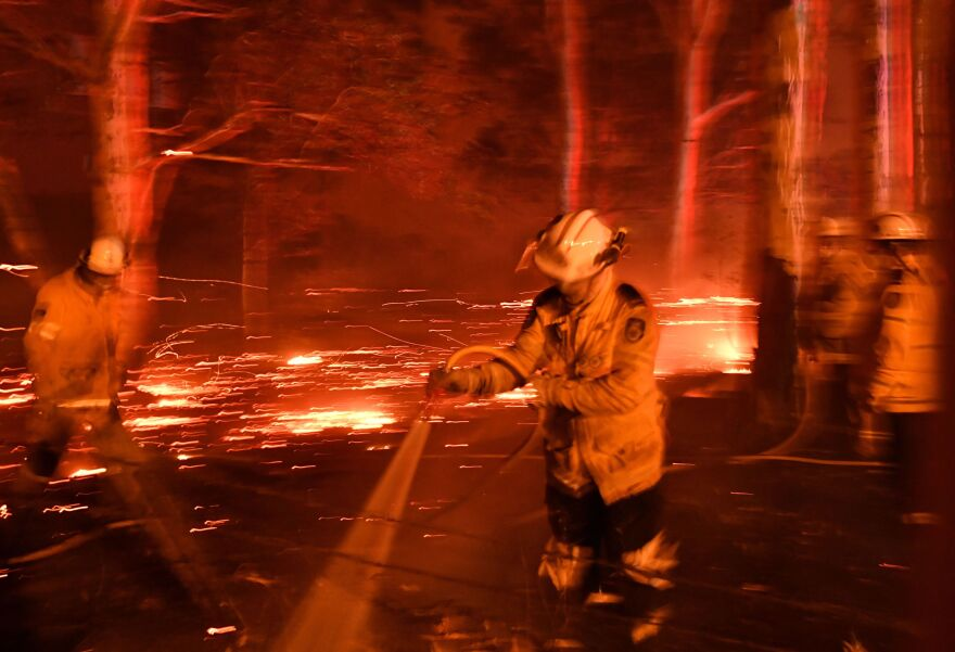 Firefighters hose down the area as they battle bush fires around Nowra in the Australian state of New South Wales on Tuesday.