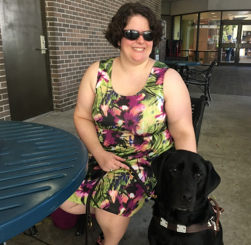 UNF writing professor Emily Michael poses with her service dog York after class, Friday.