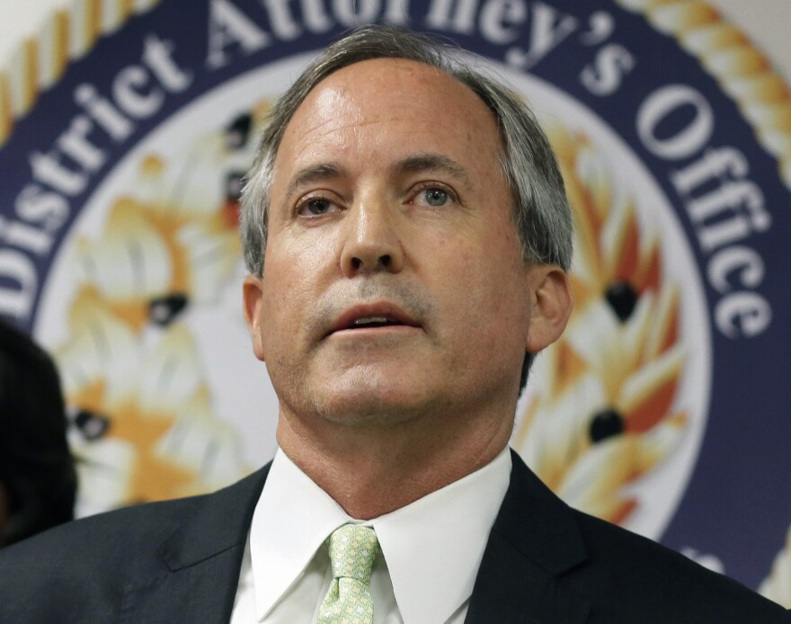 Ken Paxton looks ahead in front of a sign that says District Attorney's Office.