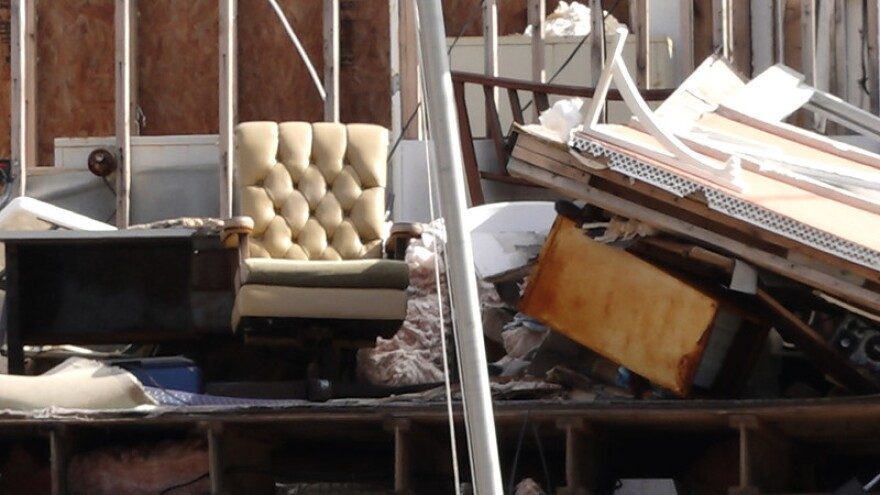What remains of this home is a lonely, cream colored chair amid skeleton walls.