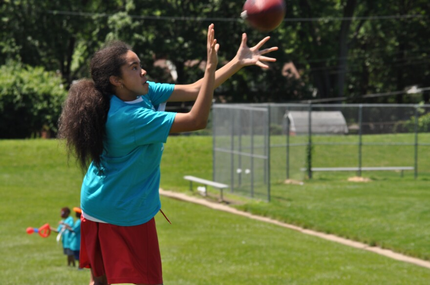Danielle Kain, 12, catches a football during the first day of summer camp at the Boys & Girls Club at Ferguson Middle School.