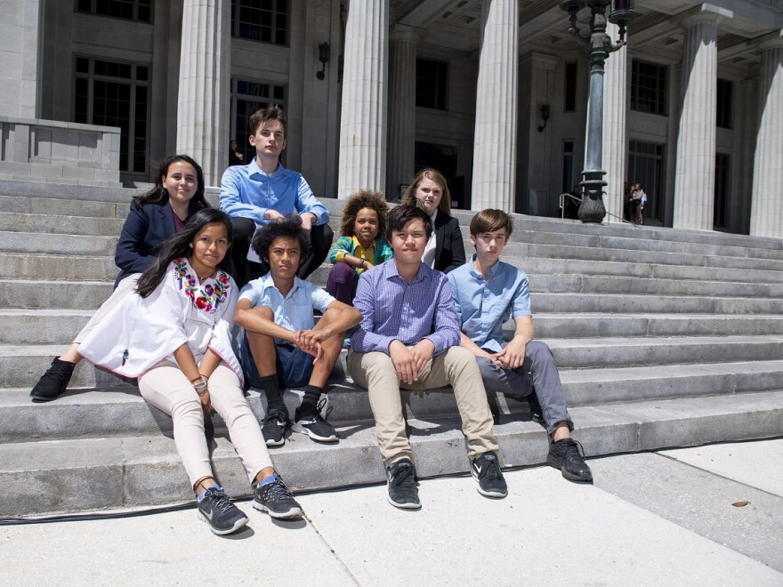 8 young people who are suing the state over climate change inaction sit on the Miami Dade Courthouse steps.
