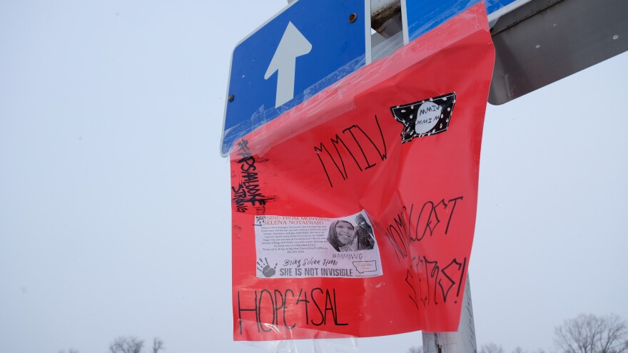 A poster with the missing notice for Selena Not Afraid blows in the wind on a blue road sign for Interstate 90.