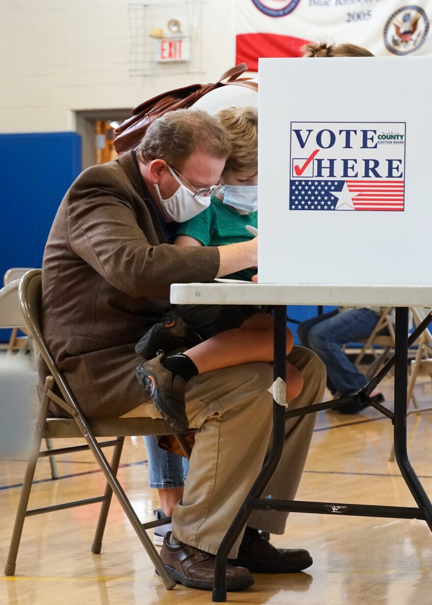 """Jake Zimmerman, Democratic primary candidate for St. Louis County executive, votes while holding his 6-year-old son Gabriel at Old Bonhomme Elementary School in Olivette on Tuesday. """"Are you voting for yourself, Dad?"""" Gabriel asked. Aug. 4, 2020"""