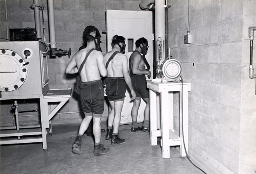 Three test subjects enter a gas chamber, which will fill with mustard gas, as part of the military's secret chemical warfare testing in March 1945.