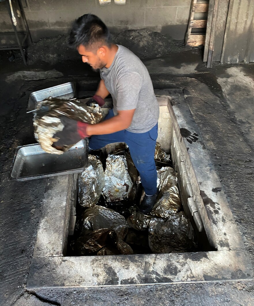 A kitchen employee hauls another beef head from the pit. Vera's is believed to be the last restaurant in Texas that cooks <em>barbacoa de pozo </em>the traditional way — underground.