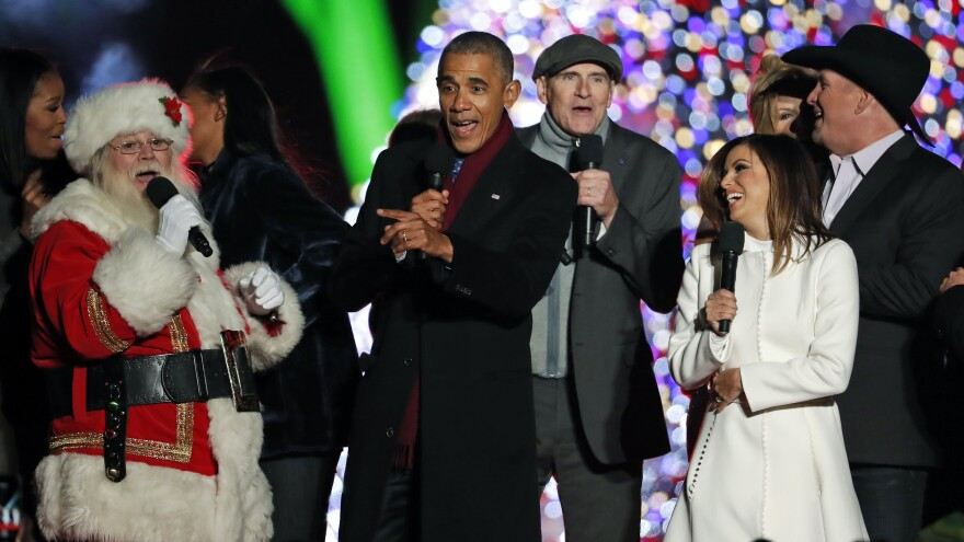 """President Obama sings """"Jingle Bells"""" with Santa, James Taylor, Eva Longoria, and Garth Brooks during the lighting ceremony for the 2016 National Christmas Tree."""