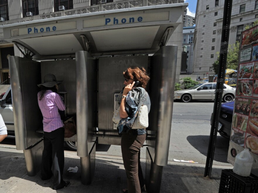 People use pay phones in Lower Manhattan.