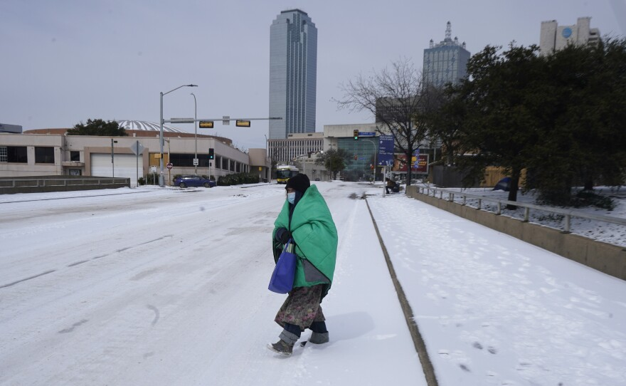 A woman wrapped in a blanket crosses the street near downtown Dallas on Tuesday. Northern Texas was likely experiencing its most severe cold snap so far this century, according to member station KERA in Dallas.