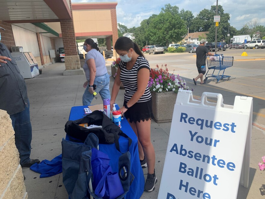 """A woman stands in front of a table with a blue table cloth on it. In front of her is a sign that says """"Request Your Absentee Ballot Here."""""""