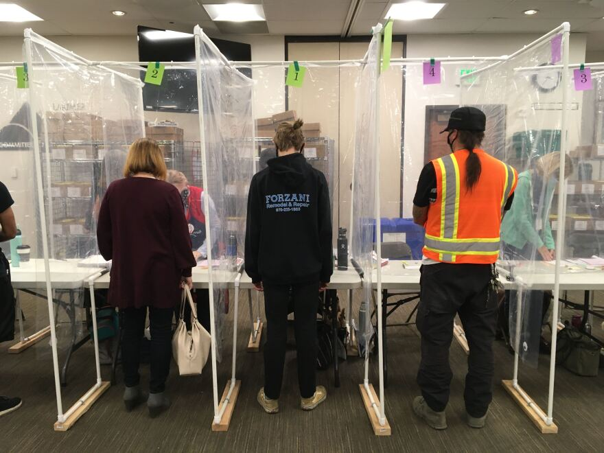 Voters stand at tables at the Larimer County Courthouse to speak with election workers. Plastic sheeting separates each person from one another.