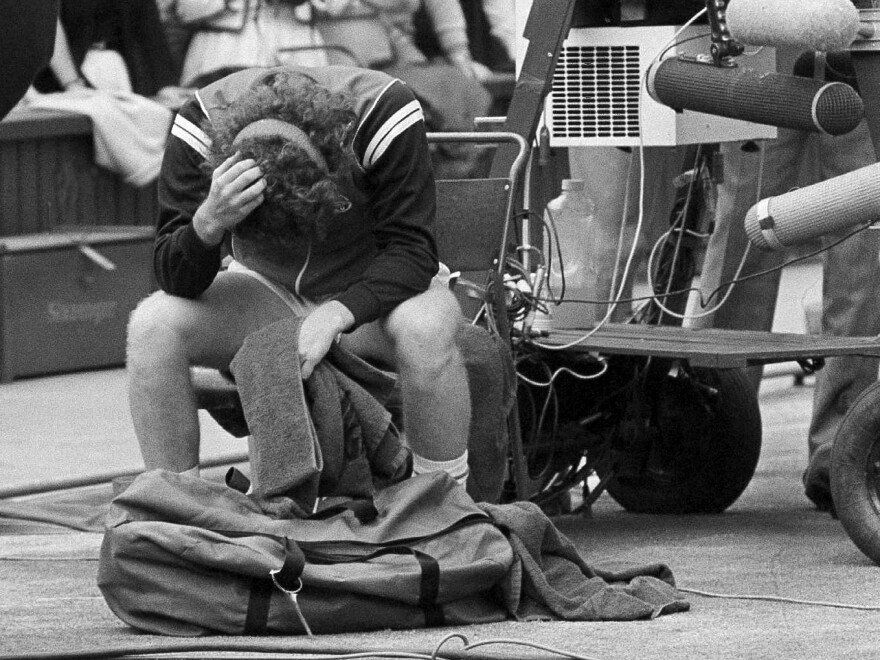 John McEnroe holds his head in his hands after being beaten by Sweden's Björn Borg.