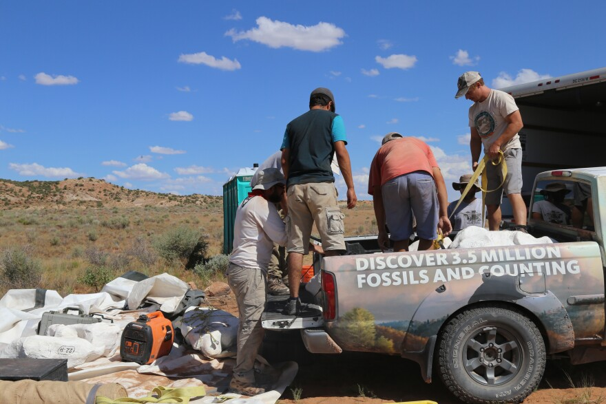 Photo of scientists loading fossils.