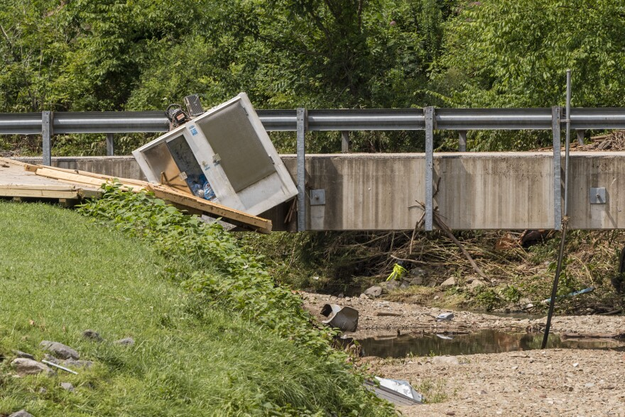 An ice cooler sits wedeged into a bridge along Fish Creek in Hundred, Wetzel County, W.Va., after flash floods hit the area early on July 29, 2017.