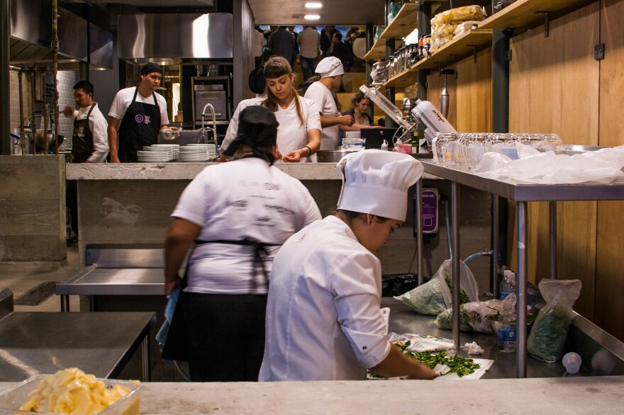 Cooks prepare dinner for a gourmet soup kitchen that feeds people with what society has thrown away as leftovers. This concept was created by chef Massimo Bottura at his restaurant RefettoRio Gastromotiva in Rio de Janeiro.