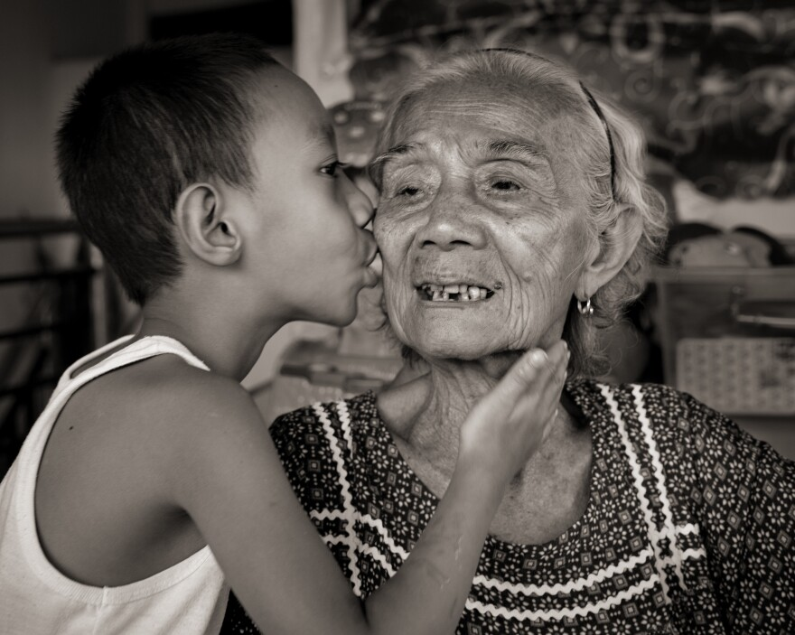 "Narcisa Claveria receives a gentle kiss from her great-grandson, Joseph Tena, 8, whom she and her husband have raised since his father died when he was an infant. Claveria was 12 when Japanese soldiers took her as a sex slave for 1 1/2 years. They raped her mother and skinned her father alive before burning down their house. She could hear him scream, ""Children, where are you? I'm in such pain."""