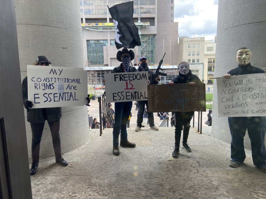 About 75 people wearing masks and carrying signs protest outside the Ohio Statehouse on Thursday, April 9, 2020, in Columbus, Ohio.