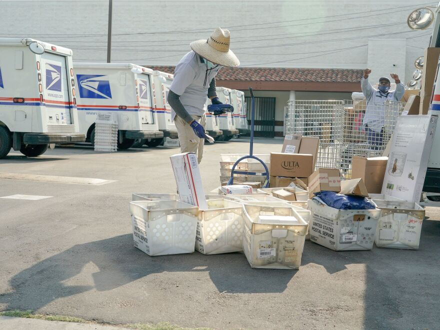 Postal workers sort, load and deliver mail at a United States Postal Service location in Los Angeles, Calif.