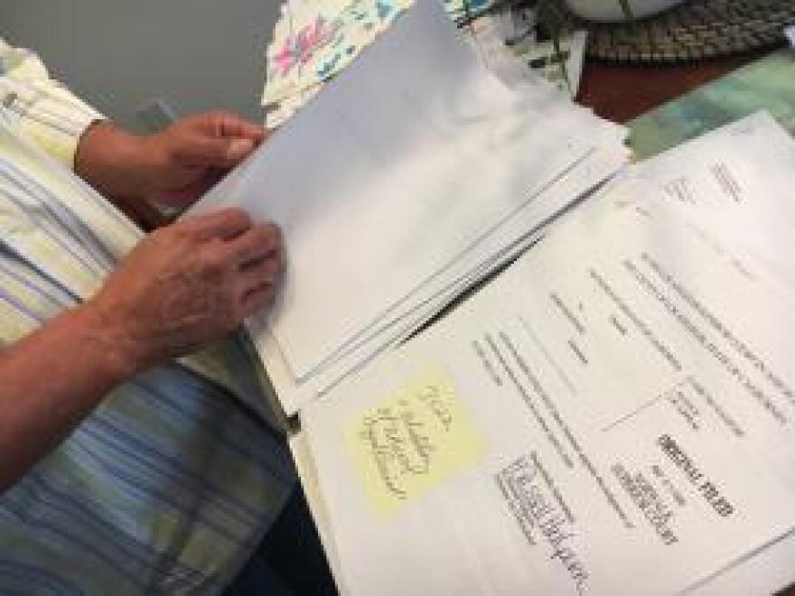 Army veteran Mario Martinez looks through papers from his criminal case in the dining room of his home in Southeast Los Angeles. Currently without a lawyer, he's trying to fight a deportation order.
