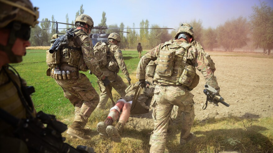U.S. soldiers carry a comrade injured by an improvised explosive device, or IED, in Logar province, south of Kabul, on Oct. 13. Roadside bombs are one of the biggest threats facing U.S. and Afghan troops, and insurgents keeping finding inventive ways to disguise them.