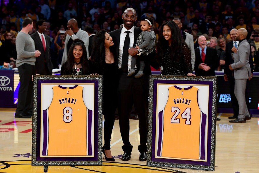 Kobe Bryant poses with his family at halftime after both his #8 and #24 Los Angeles Lakers jerseys are retired at the Staples Center on Dec. 18, 2017, in Los Angeles.