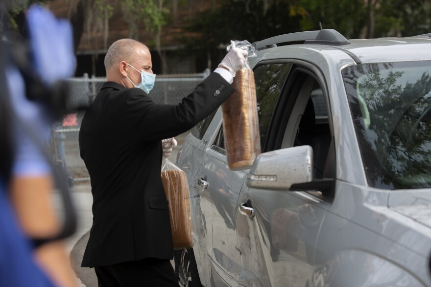 a man wearing a suit and mask hands loaves of bread to a family through their car window.