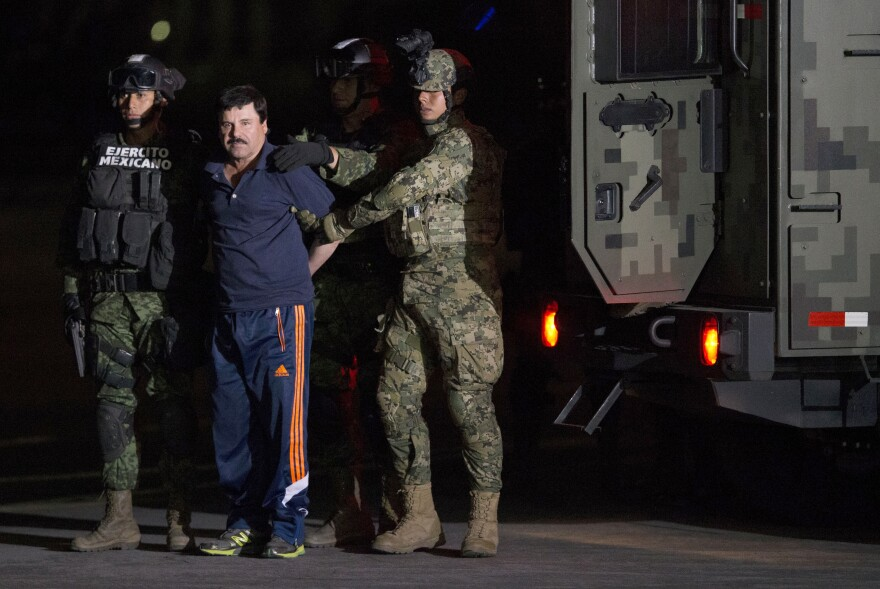 "Mexican drug lord Joaquin ""El Chapo"" Guzman is escorted by army soldiers to a waiting helicopter, at a federal hangar in Mexico City Friday. The world's most wanted drug lord was recaptured six months after he fled through a tunnel from a maximum security prison in a made-for-Hollywood escape that deeply embarrassed the government and strained ties with the United States."