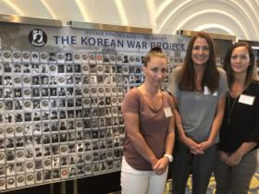 Jennifer Castaldi (center) stands in front of a display of American MIAs with he daughter Jessica Dillon (left) and friend Aly Rivers.