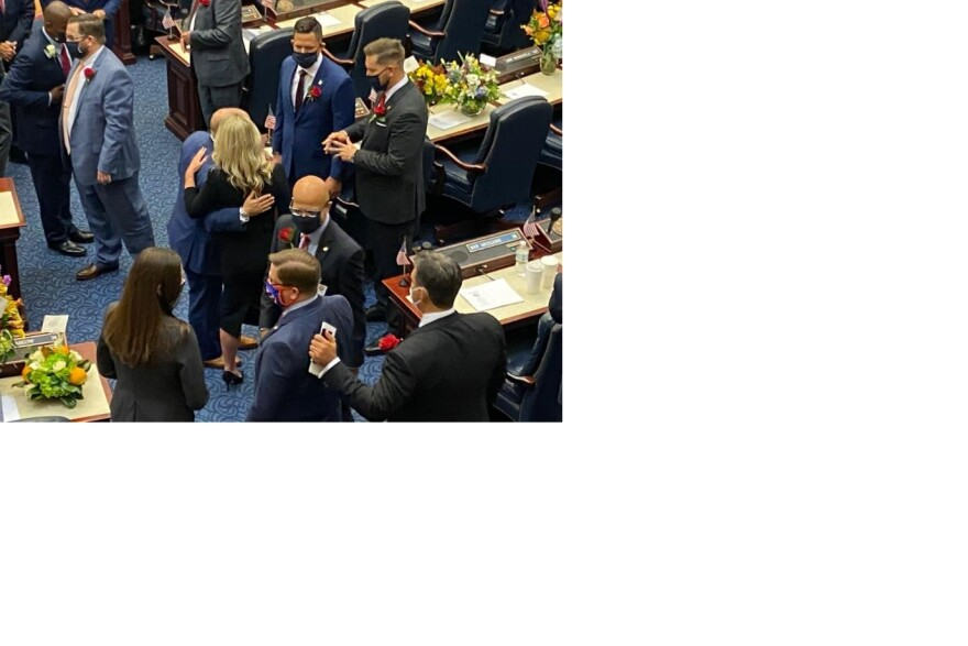 Florida lawmakers greet each wearing masks during their organizational session following the November elections.