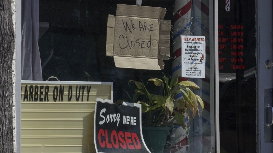 Closed signs are seen Wednesday in businesses in Milwaukee. The coronavirus pandemic has left millions out of work.