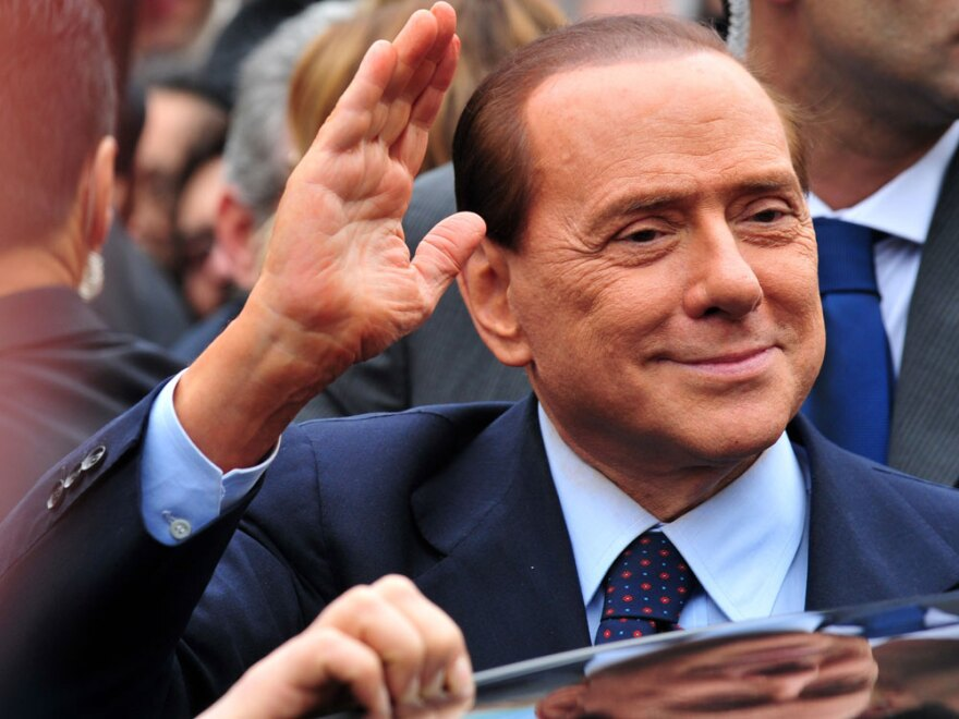 Italian Prime Minister Silvio Berlusconi acknowledges his supporters at legal hearing over allegations of fiscal fraud and breach of trust in his business interests on March 28 at Milan's justice court.