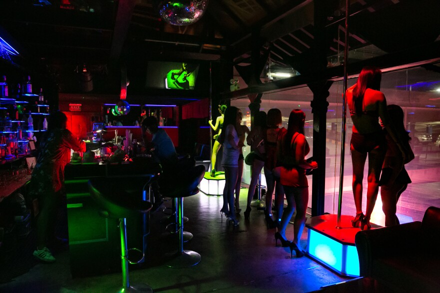 Working in the bars of the red-light district pays more than many office jobs or other service work that the women and men in Thailand's sex industry would otherwise qualify for. Above: Women dance at a bar in the Patpong red-light district in Bangkok.