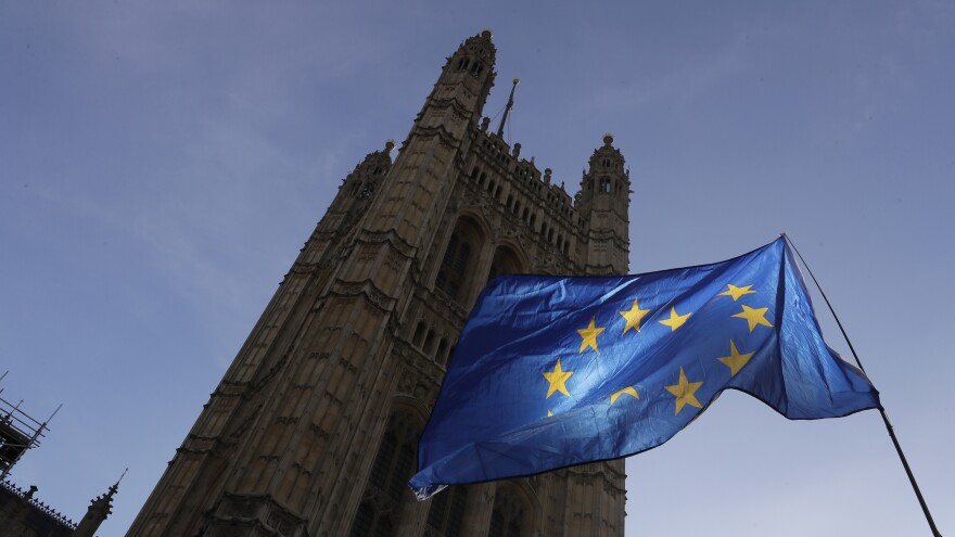 A European Union flag flies Monday outside the Parliament building in London. The multinational bloc has agreed to grant the U.K. another Brexit delay, bumping the deadline to the end of January.