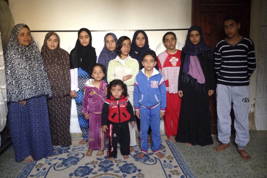 Fatiyeh abu Gamar, far left, stands with her 11 children. Their father — her husband — was killed while working as a guard at the school in Jabaliya.