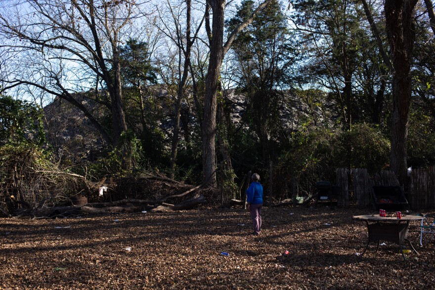 Marsha Jackson, who wears a royal blue shirt, stands in her backyard and stares straight ahead at the giant pile of shingles known as Shingle Mountain.