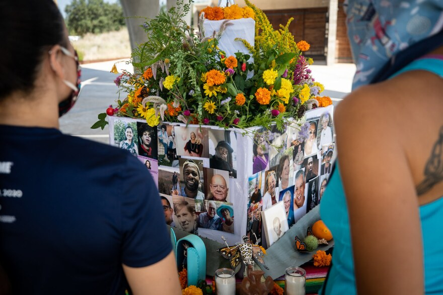 two women stand in front of a box with images of people who've passed away this year with flowers on top