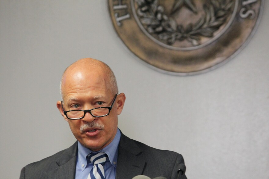Dallas District Attorney John Creuzot talking during a press conference, in front of a partially visible bronze State of Texas seal.