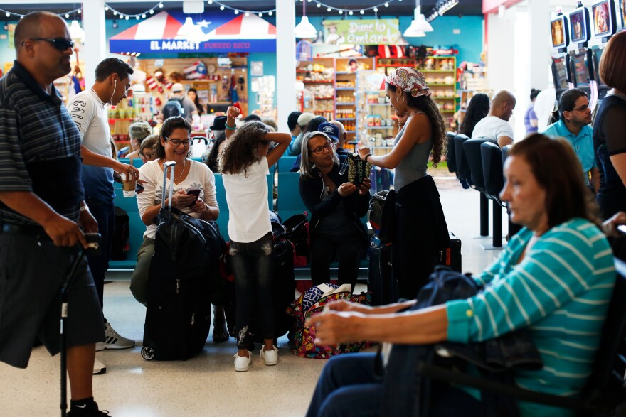 Glisela Vega Rivera and her three children wait to board a flight to Miami. Thousands of Puerto Ricans have poured into Florida after Hurricane Maria. More than 27,000 have arrived through Port Everglades and the Miami and Orlando airports alone since Oct. 3, according to the governor's office.