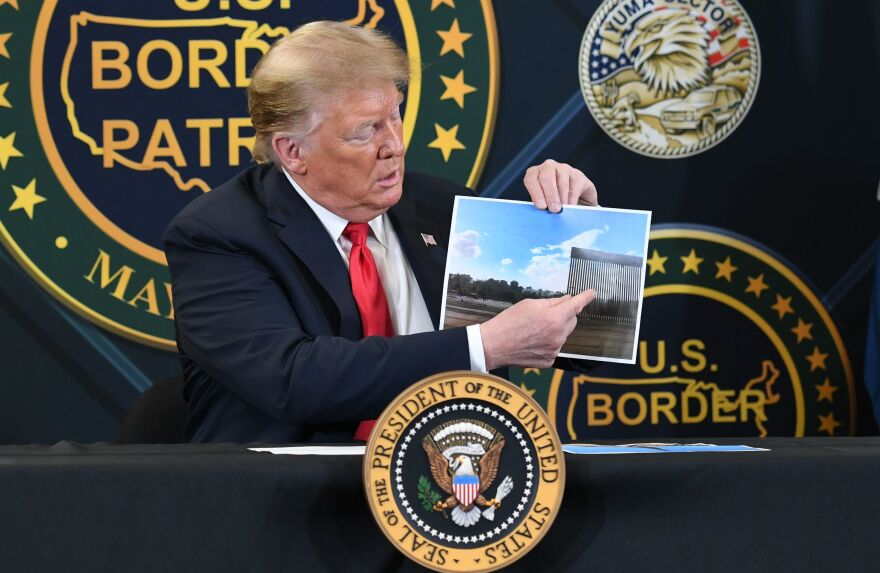 President Trump shows a photo of the wall along the southern border during a roundtable briefing on border security Tuesday in Yuma, Ariz.