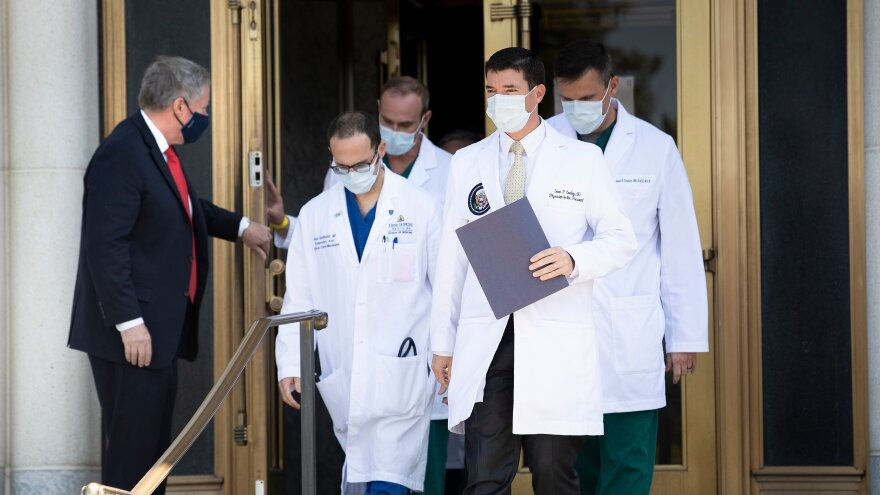 White House chief of staff Mark Meadows holds the door for White House physician Dr. Sean Conley (center) and other members of the president's medical team ahead of a briefing for reporters on Sunday.