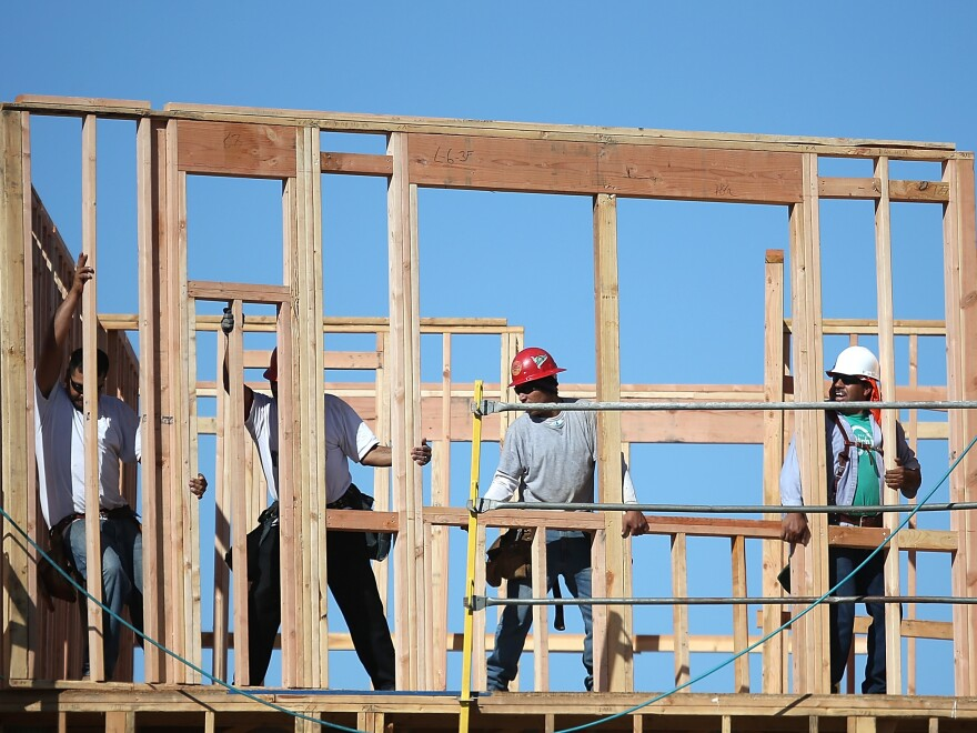 Construction workers move a framed wall into place at a new housing development in San Mateo, Calif.