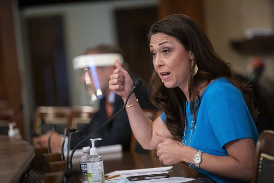 Rep. Jaime Herrera Beutler is sitting in front of a microphone wearing a blue shirt. She is holding her thumbs up.