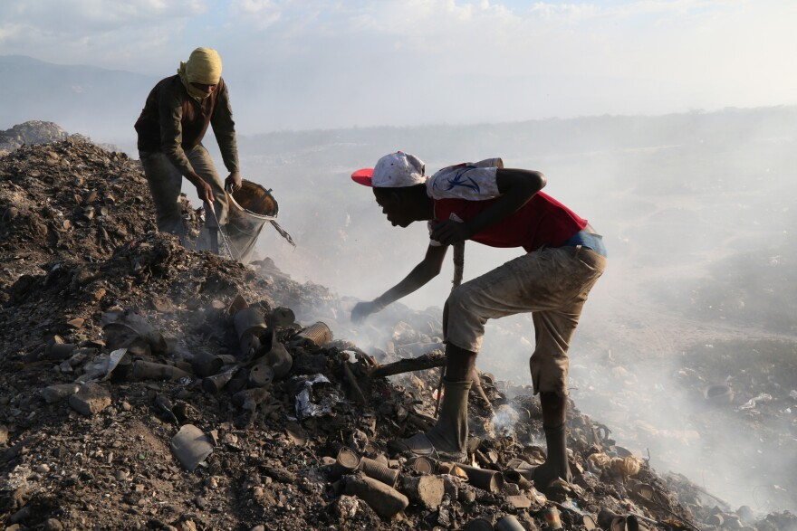 At the city landfill, men look for metal near the edge of a pit that used to be full of raw sewage. Construction delays at the Titanyen sewage treatment plant meant that raw sewage continued to be dumped at the landfill for months after the cholera epidemic began in 2010.