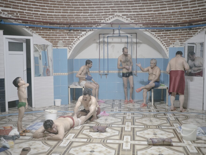 """A traditional Turkish <em>hammam</em>, or bathhouse, in Urmia. People use the bathhouses not only for relaxing, but also as a meeting place, Mann says. But traditional <em>hammams</em> are dying out. In the foreground, an employee massages a guest's leg. Mann says: """"And it really hurts. I also did it and it's not so relaxing. They are really strong."""""""