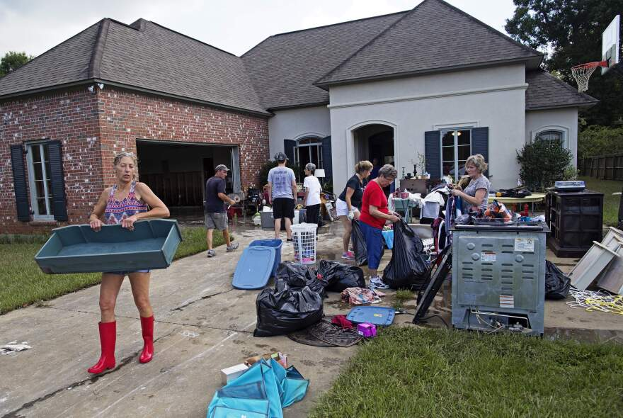 Raven Harelson, 59, (left) carries a drawer to the trash heap in front of the home of Sheila Siener, 58, as friends and family help to clean out the flood-damaged home in St. Amant, La., on Saturday.