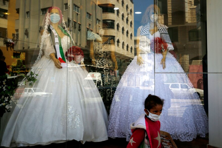 Mannequins dressed in wedding gowns and wearing protective face masks in Gaza City in March. With wedding halls closed and public gatherings forbidden to prevent the spread of the virus, many couples have celebrated their marriage in alleyways and apartments — so grooms can save the fortune they're normally expected to spend on big parties.