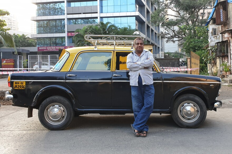 Cabbie Abdul Kareem poses with his Premier Padmini taxi — one of only about 50 that were still on Mumbai's streets as of December. Once ubiquitous, the Padmini is being replaced by modern cars.